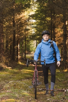 Cyclist in a blue coat and a helmet in the park with tall trees