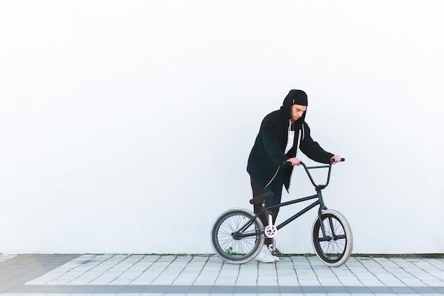 Велосипедист bmx на белой стене. bmx райдер с велосипедом на белом