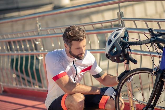 自転車のホイールをチェックするサイクリスト