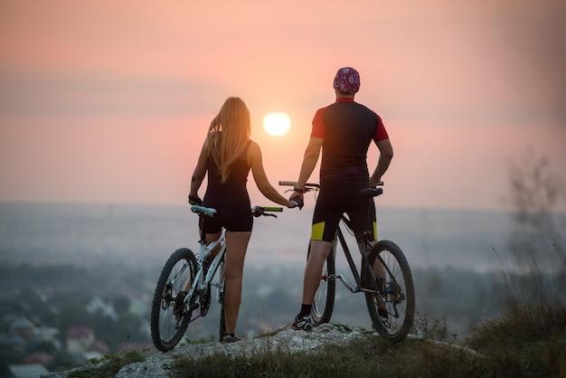 Cyclist couple mountain bikes on rock