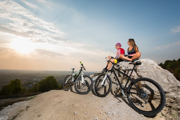 Cyclist couple in the sunglasses sitting on a rock near bikes, looking to the sun.