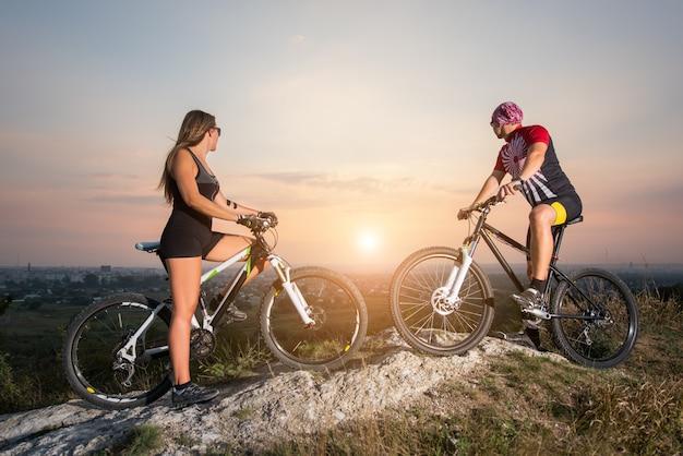 Пары велосипедиста при горные велосипеды стоя на холме под небом вечера и наслаждаясь ярким солнцем на заходе солнца.