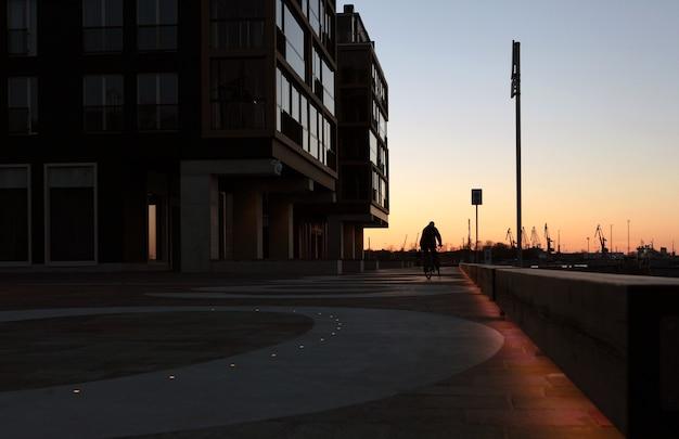 항구 지역 탈린 시의 현대적인 칼라마자 지구에서 야간 스카이라인 앞에서 자전거를 타는 사람