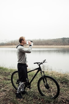 Cyclist drinking water from bottle standing near the lake