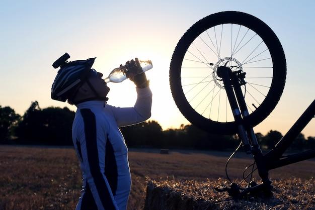 사이클리스트는 석양에 대하여 병에서 물을 마신다