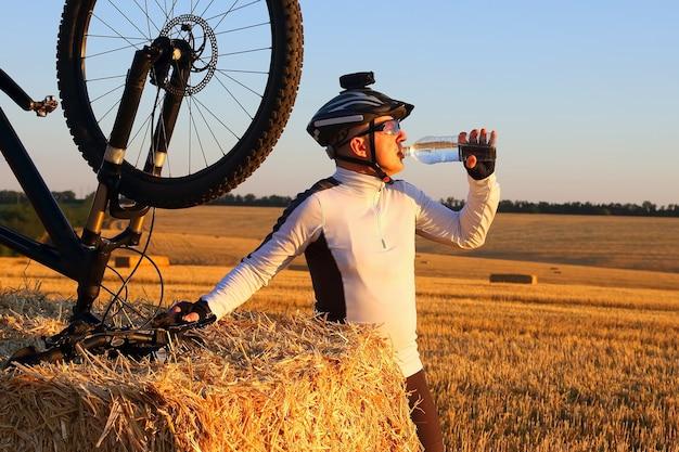 サイクリストは日光の下でボトルから水を飲みます