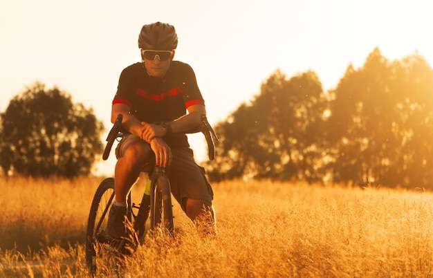 Cyclist on a gravel bike in a field against the backdrop of a dramatic sunset