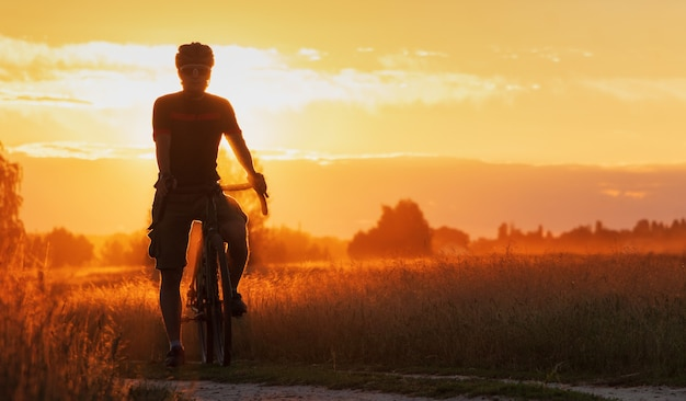 Cyclist on a gravel bike stands in a field on a dramatic sunset. beautiful landscape of young sports guy silhouette with bicycle in the field in the evening.
