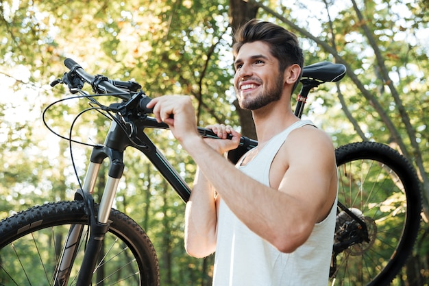 Cyclist holding bicycle in forest
