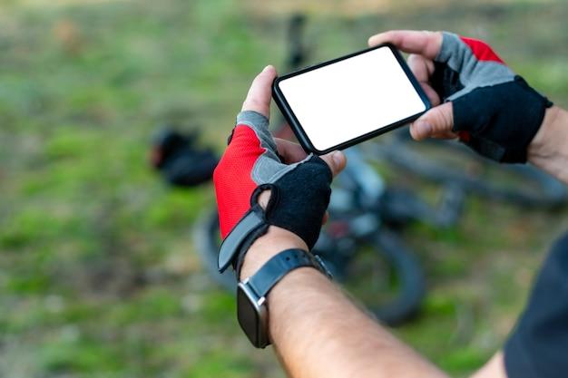 자전거 타는 사람은 자연 속에서 자전거를 배경으로 손에 흰색 스크린이 있는 모형 스마트폰 클로즈업을 들고 있습니다.