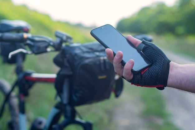 Cyclist holds a smartphone close-up in his hands on the background of a bicycle in nature.