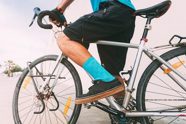 都市環境のサイクリストレジャーの下から見た青いtシャツと靴下を持った自転車に乗っている人