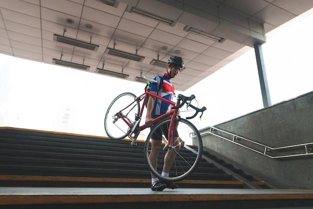 サイクリング服を着たサイクリストが自転車を手にして地下通路の階段を下りる