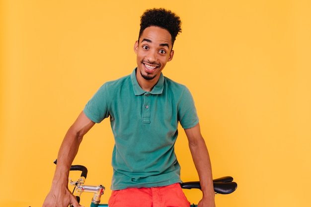 놀란 된 미소로 포즈를 취하는 녹색 티셔츠에 사이클. 자전거 근처에 앉아 놀된 검은 머리 남자의 초상화.