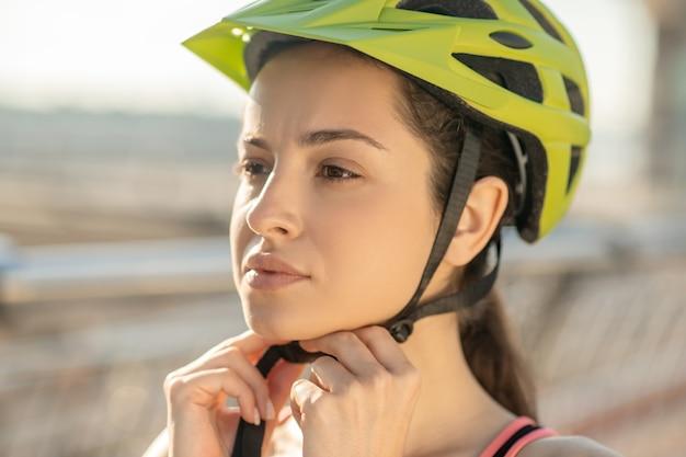 ヘルメットをかぶったサイクリスト。ヘルメットをかぶった女性サイクリストのクローズアップ写真