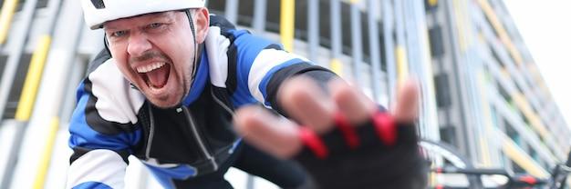 헬멧을 쓴 자전거 타는 사람이 자전거에서 떨어져 비명을 지른다
