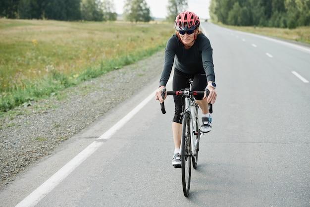 Велосипедист в шлеме, едущий на велосипеде по открытой дороге во время соревнований