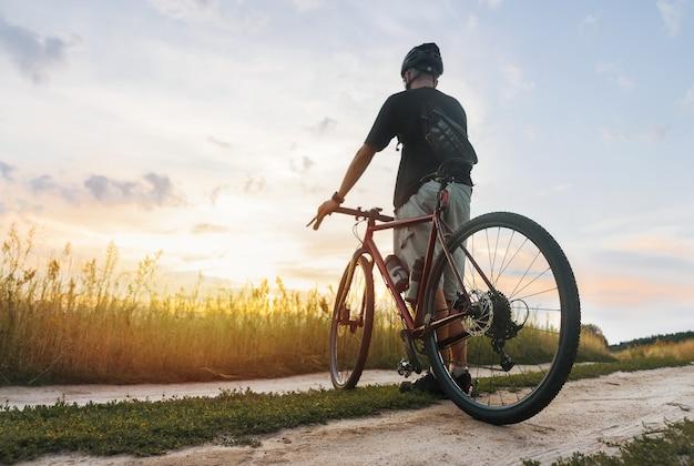 フィールドに立って、新鮮な空気でスポーツトレーニングの後に夕日を楽しんでいるヘルメットのサイクリスト。アウトドアアクティビティのコンセプト。