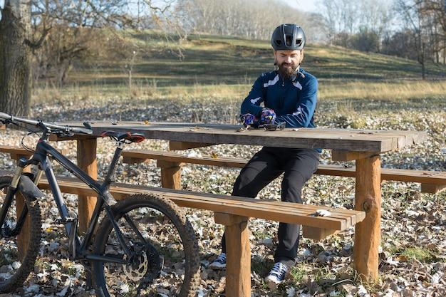 에어 서스펜션 포크가 달린 현대적인 탄소 하드테일 자전거를 타고 바지와 양털 재킷을 입은 사이클리스트는 오프로드를 탈 수 있습니다. 그 남자는 가을 공원의 벤치에서 쉬고 있다.
