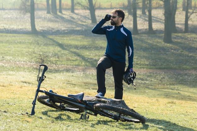 에어 서스펜션 포크가 달린 현대적인 탄소 하드테일 자전거를 타고 바지와 양털 재킷을 입은 사이클리스트는 오프로드를 탈 수 있습니다. 그 남자는 공원의 그루터기에 쉬고 있고, 멀리 보인다.