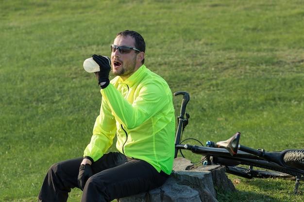에어 서스펜션 포크가 있는 현대적인 탄소 하드테일 자전거에 바지와 녹색 재킷을 입은 사이클리스트
