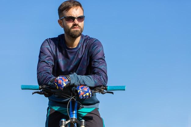Велосипедист в шортах и майке на современном карбоновом хардтейл-байке с пневмоподвеской.
