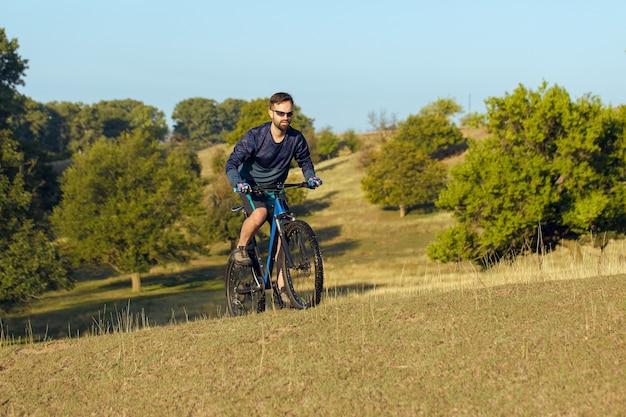 에어 서스펜션 포크가 있는 현대적인 탄소 하드테일 자전거를 타는 반바지와 저지를 입은 사이클리스트