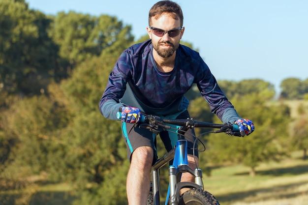 에어 서스펜션 포크가 있는 현대적인 탄소 하드테일 자전거를 타는 반바지와 저지를 입은 사이클리스트 프리미엄 사진