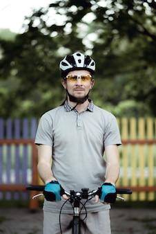 스포츠웨어와 헬멧의 사이클리스트는 공원의 도로에 서서 정면을 바라보고 있습니다.