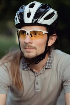 스포츠웨어와 헬멧을 착용 한 사이클리스트가 공원의 길에 서서 옆을 바라 봅니다.