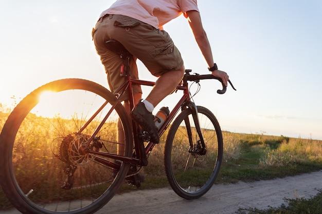 Велосипедист в поле. молодой спортивный человек едет на своем велосипеде на закате с солнечным лучом.