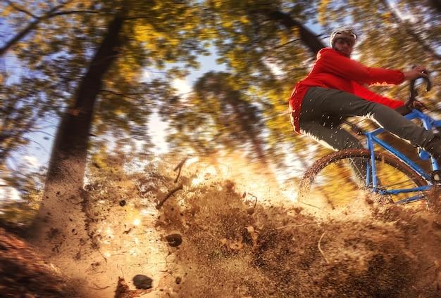 森の中のサイクリストがトレイルに沿って走り、スキッド後に後輪からほこりを持ち上げます。