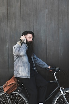 Cyclist listening music on headphones standing against black wooden wall
