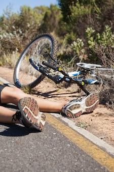 Велосипедист, лежащий на дороге после аварии