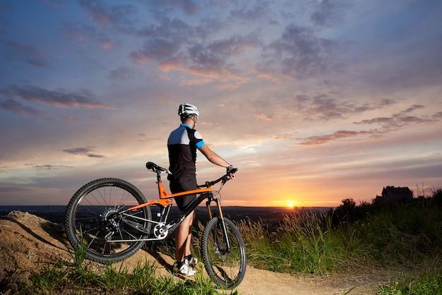 헬멧에 자전거 타는 사람 일몰의 배경에 달려있다