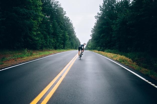 Uomo ciclista in sella a una bicicletta sulla strada