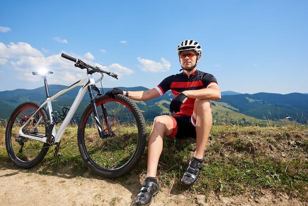 Велосипедист возле своего велосипеда