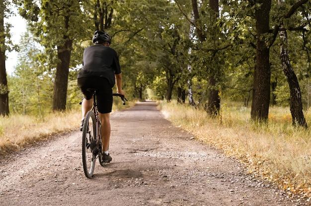 砂利自転車に乗ったサイクリストは、ピットのある田舎道を走ります。アウトドアスポーツ活動。