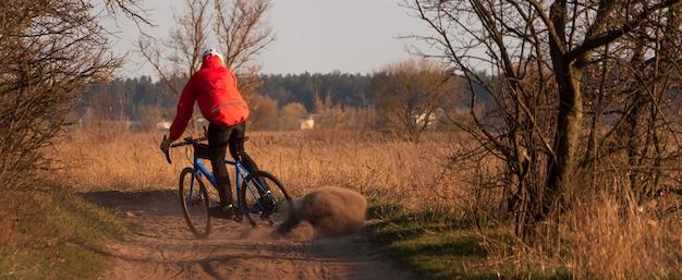 砂利自転車のサイクリストが道路に沿って走り、日没時に後輪からほこりを持ち上げます。砂利自転車。