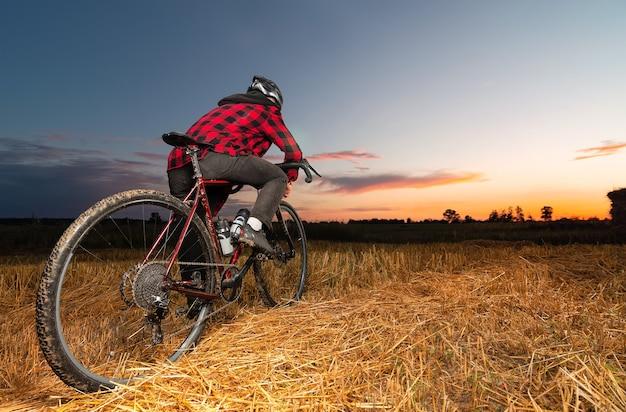 砂利自転車のサイクリストは、美しい夕日のフィールドに立っています