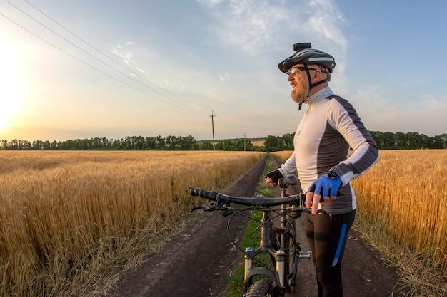 자전거에 자전거 타는 사람은 일몰을 본다. 스포츠와 취미. 야외 활동
