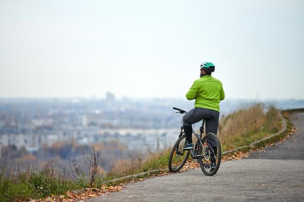 都市の景観、背面図、コピースペースを見て丘の上にサイクリスト