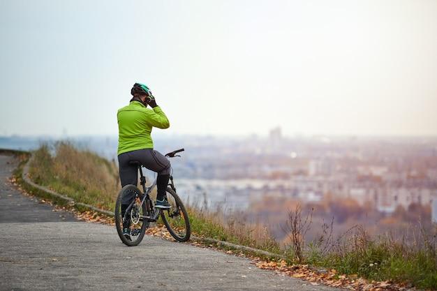 街並みを見ている丘の上にサイクリスト