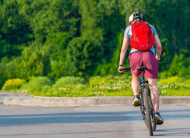 屋外でレーシングバイクをペダリングするサイクリスト。夏の日の背景で動いているサイクリストの画像。