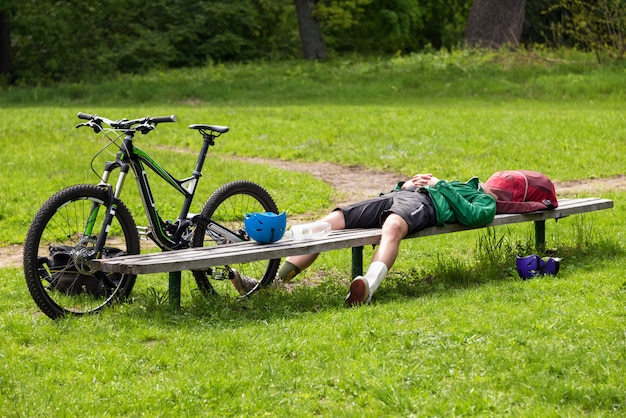 Cyclist resting on a bench in the park. tired young man with his mountain bike in the forest resting and making pause
