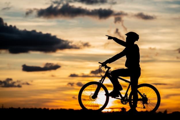Siluetta di riposo del ciclista al tramonto. concetto di sport all'aperto attivo