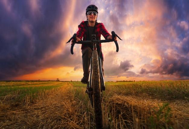 サイクリストは日没時にフィールドで自転車に乗る。フロントローアングルビュー。