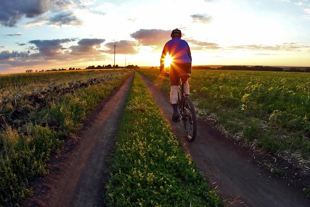 Велосипедист едет на велосипеде по трассе на закате