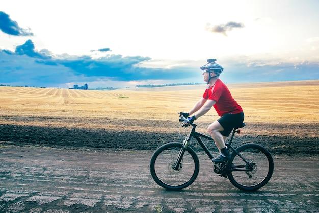 자전거 타는 사람은 들판 근처의 도로에서 자전거를 탄다. 야외 운동. 건강한 생활.