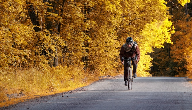 サイクリストは、黄色の葉のある秋の森で自転車に乗って道路に沿って乗ります。